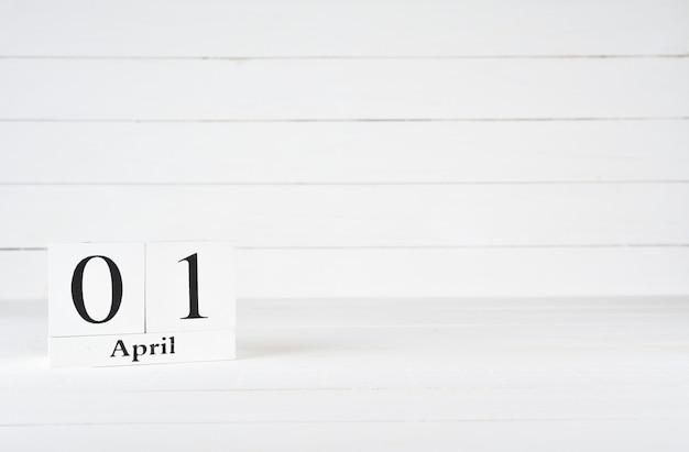 1. april, tag 1 des monats, geburtstag, jahrestag, holzblockkalender auf weißem hölzernem hintergrund mit kopienraum für text.