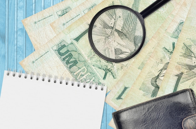 1 brasilianische echtgeldscheine und lupe mit schwarzer brieftasche und notizblock