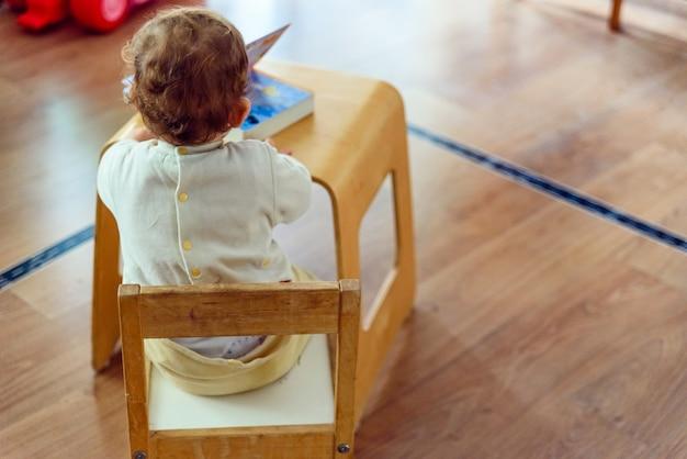 1-jähriges baby, das auf seinem rücken in einem stuhl sitzt, um ein buch zu lesen