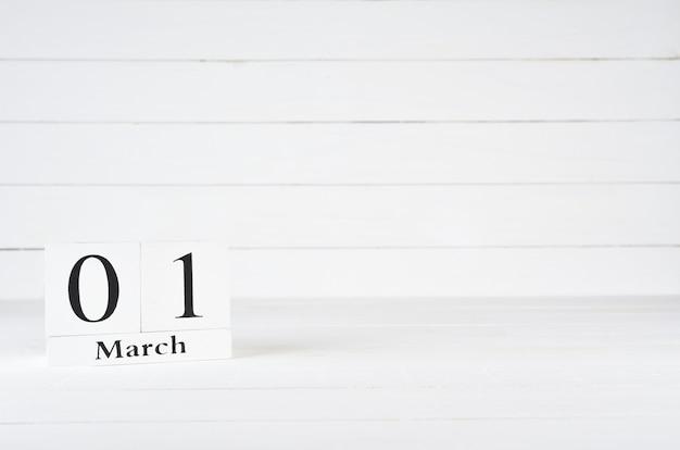1. märz, tag 1 des monats, geburtstag, jahrestag, holzblockkalender auf weißem hölzernem hintergrund mit kopienraum für text.