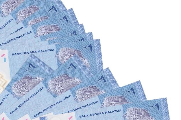 1 malaysische ringgit-rechnungen liegen isoliert auf weißer wand mit kopienraum, der in fächernahaufnahme gestapelt wird. zahltagzeitkonzept oder finanzoperationen