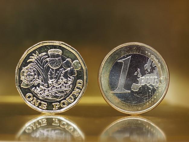 1-pfund- und 1-euro-münze über metallhintergrund