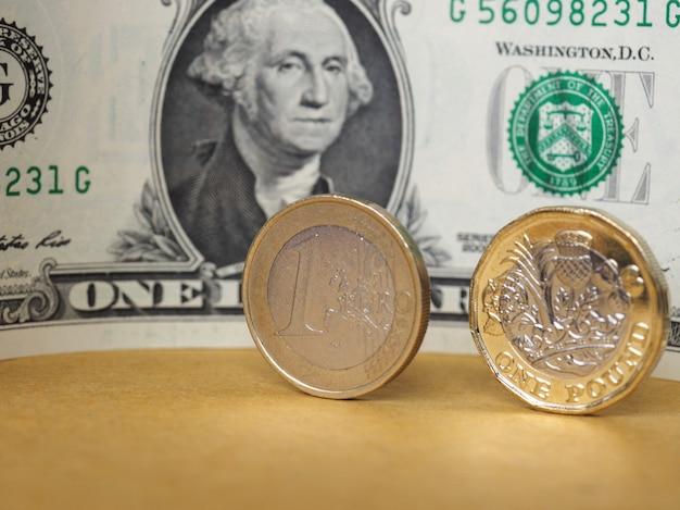 1-pfund- und 1-euro-münze und eine dollarnote über metallhintergrund