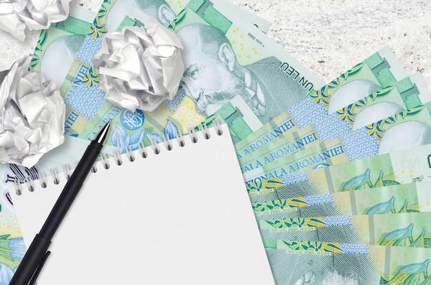 1 rumänische leu-scheine und zerknitterte papierkugeln mit leerem notizblock. schlechte ideen oder weniger inspirationskonzept. ideen für investitionen suchen