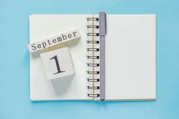 1. september auf einem hölzernen kalender auf studienlehrbuch auf blau. zurück zum schulkonzept