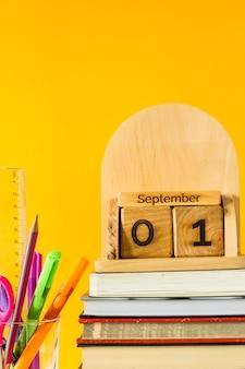 1. september auf einem hölzernen kalender unter lehrbüchern und stiften, um auf einem gelben hintergrund zu studieren