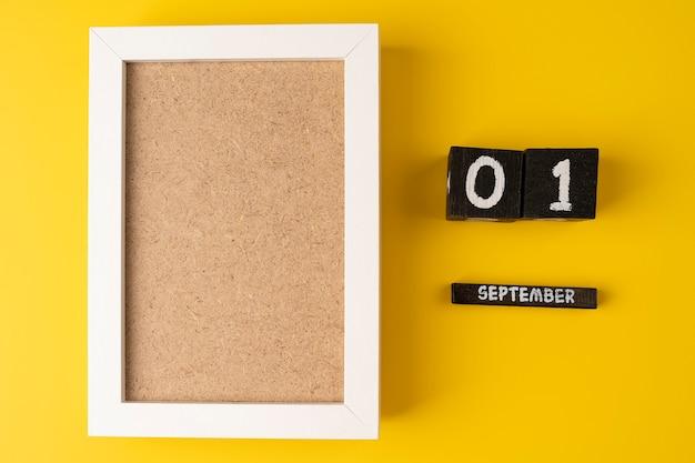 1. september auf einem holzkalender auf gelbem hintergrund mit leerem weißen bilderrahmen zurück zur schule