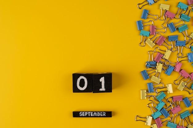 1. september auf einem holzkalender unter farbigem clip für papier auf einem gelben hintergrundkopierraum