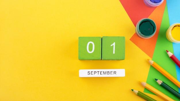 1. september auf einem holzkalender zwischen buntstiften und farben