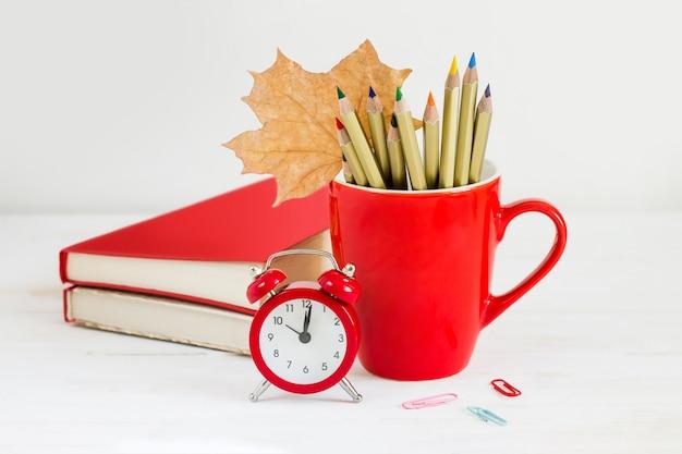 1. september konzept. roter wecker, tasse, farbstifte, bücher und ahornblatt. zurück zum schulkonzept