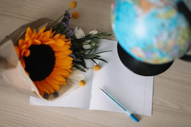 1. september zurück zum schulkonzept blumenstrauß mit sonnenblumen und schulmaterial auf dem tisch