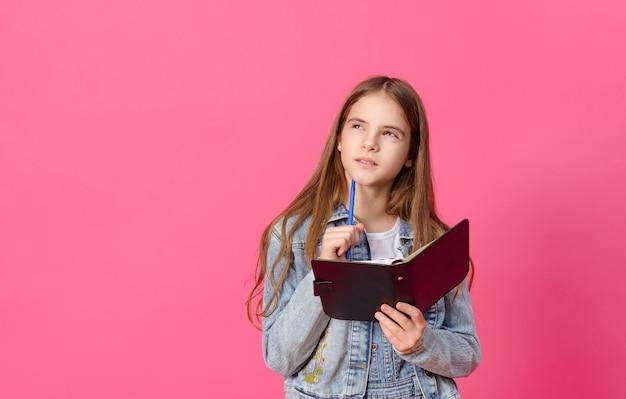 1 süßes nachdenkliches weißes mädchen 10 jahre alt in einer blauen jeansjacke mit einem notizbuch und einem stift auf einer rosa oberfläche