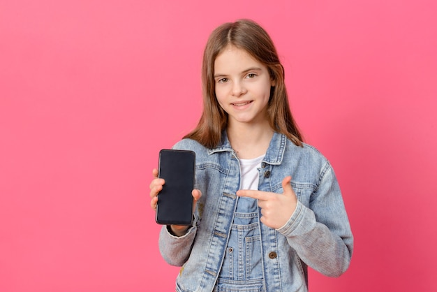 1 süßes weißes mädchen 10 jahre alt in einer blauen jeansjacke mit einem smartphone in ihren händen auf einer rosa oberfläche