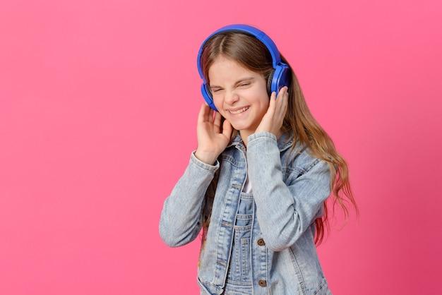1 süßes weißes mädchen 10 jahre alt in einer blauen jeansjacke mit kopfhörern auf einer rosa oberfläche