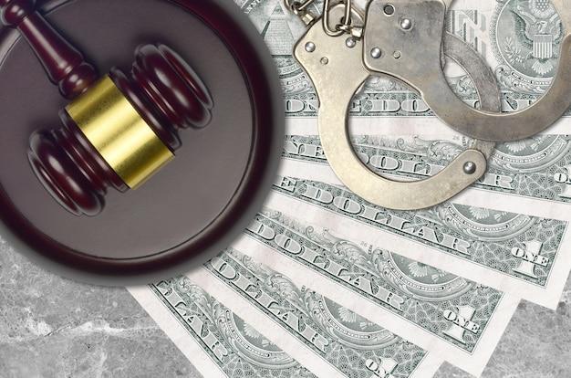 1 us-dollar-schein und richterhammer mit polizeihandschellen