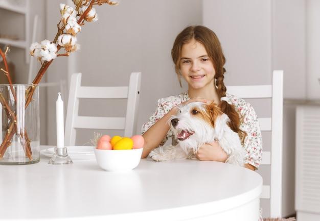 1 weißes junges mädchen 10 jahre alt sitzt am küchentisch und umarmt hund jack russell hund, ostereier,