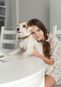 1 weißes junges mädchen 10 jahre alt sitzt am küchentisch und umarmt hund jack russells weißen pelzhund
