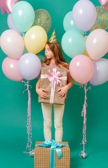 1 weißes mädchen 10 jahre alt mit einem geschenk, rosa, gelbe, blaue luftballons für einen urlaub auf einer grünen oberfläche