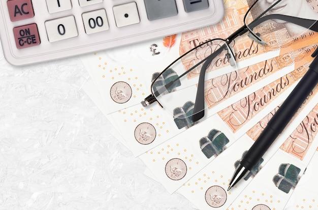 10 britische pfund rechnungen fan und taschenrechner mit brille und stift. geschäftskredit- oder steuerzahlungssaisonkonzept