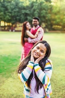 10 jahre altes indisches kleines mädchen, das in die kamera schaut, während ihre eltern sie von hinten ansehen