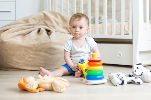 10 monate altes baby, das mit buntem spielzeugturm spielt
