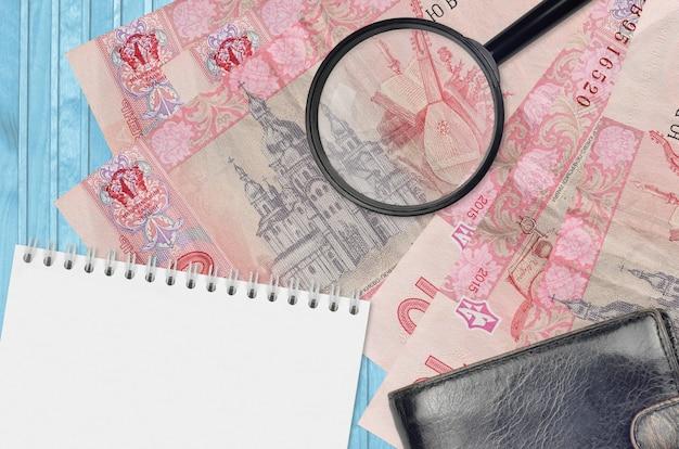 10 ukrainische griwna-scheine und lupe mit schwarzer geldbörse und notizblock