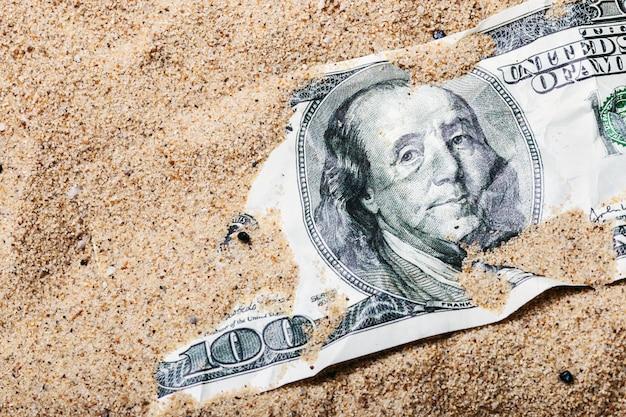 100-dollar-schein im sand begraben