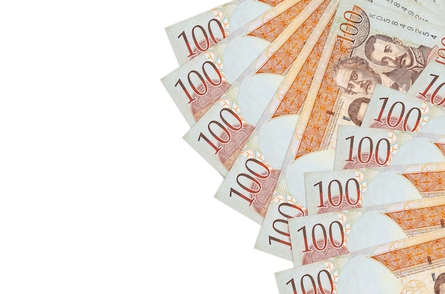 100 dominikanische peso-scheine liegen isoliert auf weißem hintergrund mit kopierraum