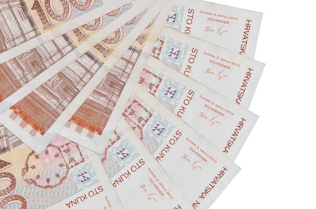100 kroatische kuna-scheine liegen isoliert auf weißer wand mit in fächerform gestapeltem kopierraum in nahaufnahme. finanztransaktionskonzept