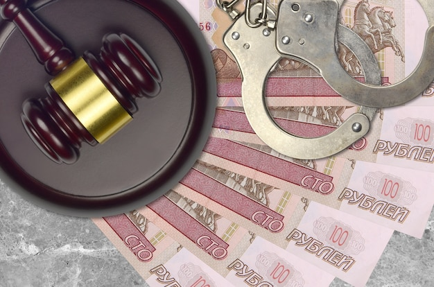 100 russische rubel rechnungen und richter hammer mit polizei handschellen auf dem schreibtisch. konzept des gerichtsverfahrens oder der bestechung. steuervermeidung oder steuerhinterziehung