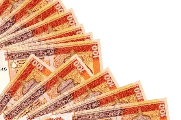 100 srilankische rupienscheine liegen isoliert auf weißer wand mit kopienraum, der in fächernahaufnahme gestapelt wird. zahltagzeitkonzept oder finanzoperationen