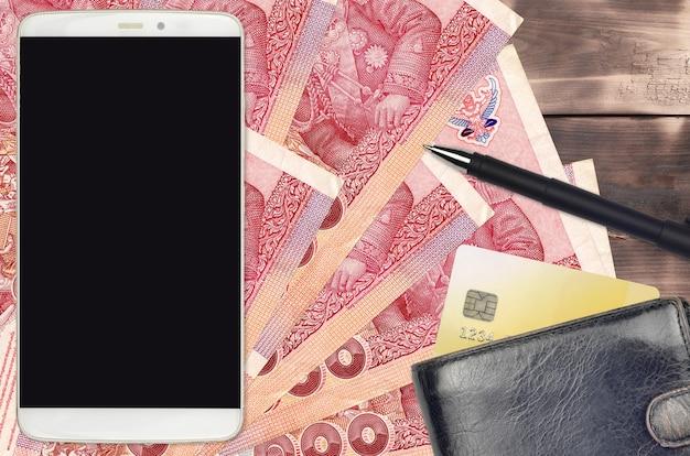 100 thai baht rechnungen und smartphone mit geldbörse und kreditkarte. e-payment- oder e-commerce-konzept. online-shopping und geschäft mit tragbaren geräten