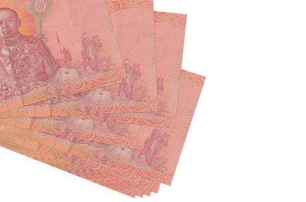 100 thailändische baht-scheine liegen in kleinen bündeln oder packungen, die auf weiß isoliert sind