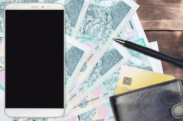 100 tschechische korun rechnungen und smartphone mit geldbörse und kreditkarte. e-payment- oder e-commerce-konzept. online-shopping und geschäft mit tragbaren geräten