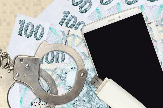 100 tschechische korun rechnungen und smartphone mit polizei handschellen. konzept von hacker-phishing-angriffen, illegalem betrug oder online-spyware-softdistribution