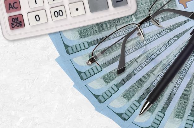 100 us-dollar-scheine fan und taschenrechner mit brille und stift. geschäftskredit- oder steuerzahlungssaisonkonzept. finanzielle planung