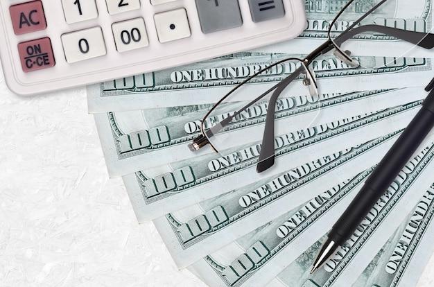 100 us-dollar-scheine fan und taschenrechner mit brille und stift. geschäftskredit- oder steuerzahlungssaisonkonzept