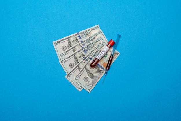 100 us-dollar-scheine und blutprobe im reagenzglas auf blau