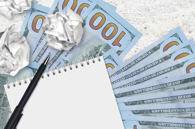 100 us-dollar-scheine und zerknitterte papierkugeln mit leerem notizblock. schlechte ideen oder weniger inspirationskonzept. ideen für investitionen suchen