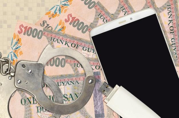 1000 guyanische dollarnoten und smartphone mit polizeihandschellen.