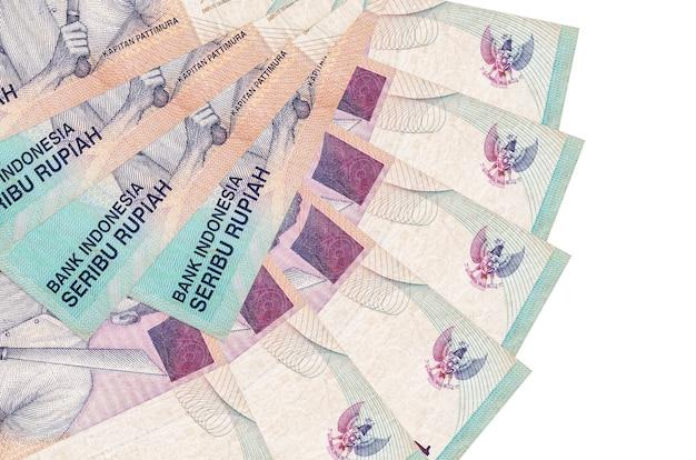 1000 indonesische rupiah-scheine liegen isoliert auf weißer wand mit in fächerform gestapeltem kopierraum in nahaufnahme. finanztransaktionskonzept