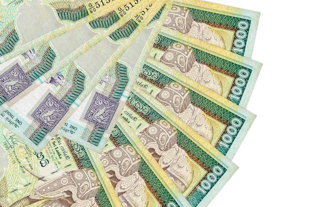 1000 srilankische rupienscheine liegen isoliert auf weißer wand mit in fächerform gestapeltem kopierraum in nahaufnahme. finanztransaktionskonzept