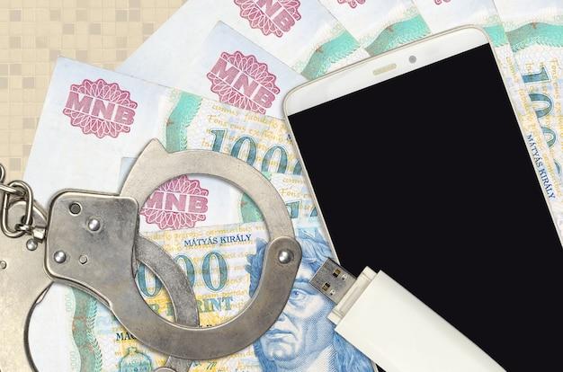 1000 ungarische forint-rechnungen und smartphone mit polizeihandschellen