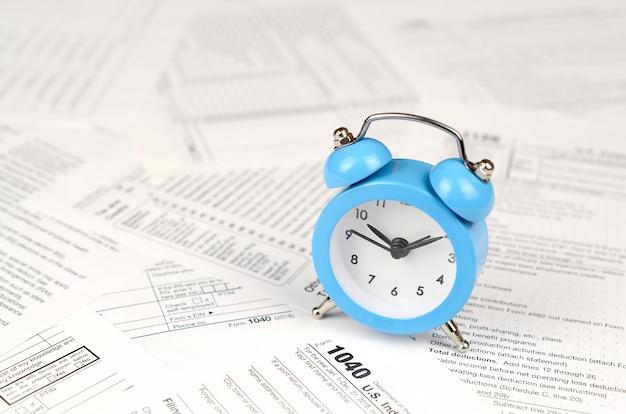 1040 einkommensteuererklärung und blauer wecker