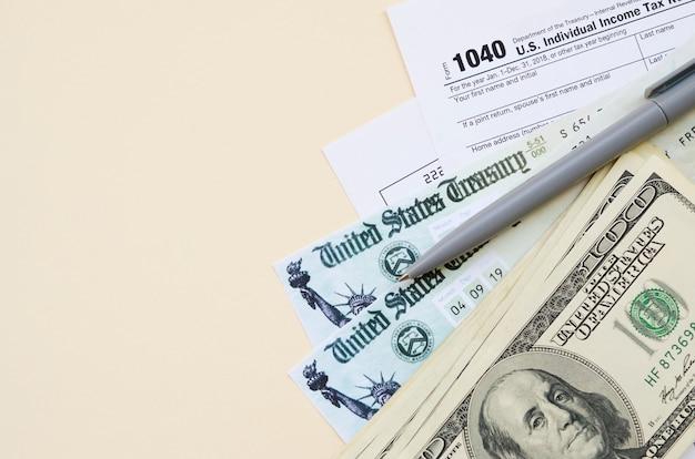 1040 formular zur individuellen einkommensteuererklärung mit rückerstattungsscheck und hundert-dollar-scheinen auf beigem hintergrund