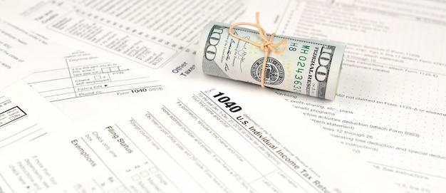 1040 individuelle einkommenssteuererklärung mit einer rolle amerikanischer dollarbanknoten