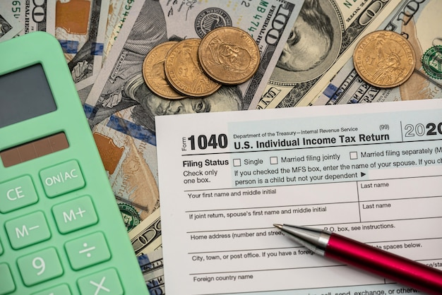 1040 individuelles einkommensteuererklärungsformular mit dollarnoten und taschenrechner. buchhaltungskonzept