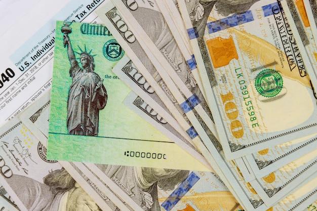 1040 steuerformular mit rückerstattungsscheck und währung us-dollar banknoten nahaufnahme