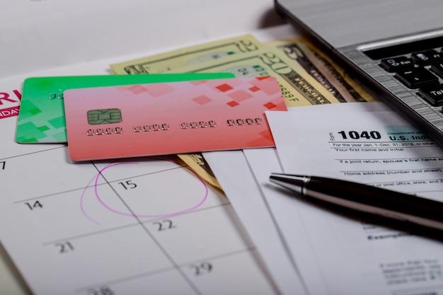 1040 us-steuerformular, geld und kalender mit us-dollar-geld und computer