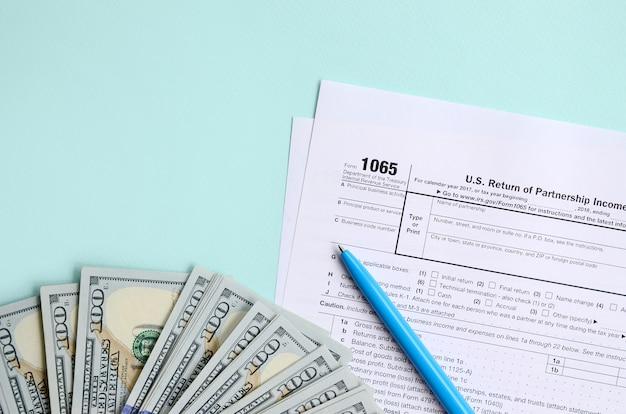 1065 steuerformular liegt nahe hundert dollarscheinen und blauem stift auf einem hellblauen hintergrund. us-rückkehr für elterneinkommen